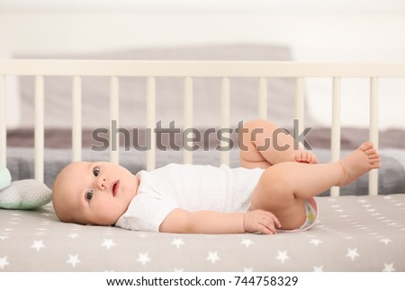 Cute baby lying in crib at home