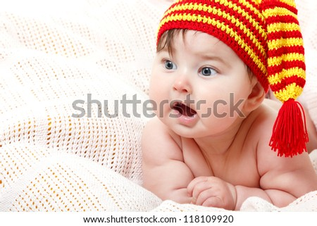 cute baby lying on pink plaid in vivid funny hat, beautiful kid's face closeup with copyspace