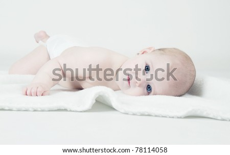 Cute baby lying on white blanket