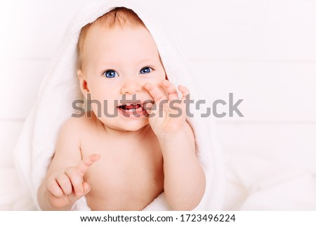 Cute baby of 8 months in a big white towel is dressed on his head. Holds fingers in the mouth. Clean little baby after bath.