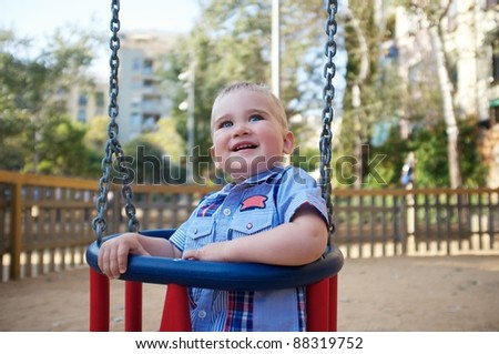Cute baby on a swing in a park