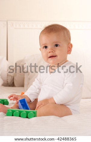 Cute baby on a white bed playing with colourful toy brick