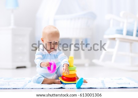 Shutterstock Cute baby playing with colorful rainbow toy pyramid sitting on play mat in white sunny bedroom. Toys for little kids. Interior for little boy nursery. Child with educational toy. Early development