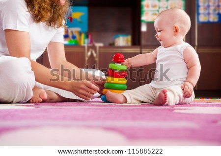 Cute baby playing with her mother on pink carpet