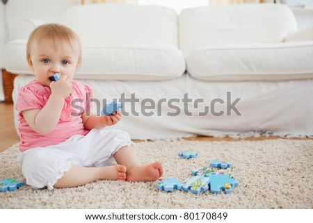Cute baby playing with puzzle pieces while sitting on a carpet in the living room