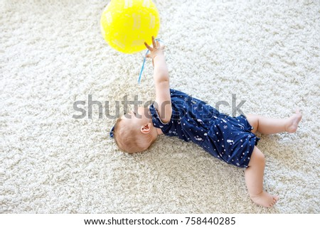 cute baby playing with red air...