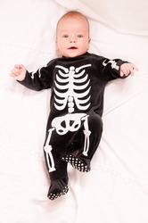 Cute baby portrait in funny skeleton suit isolated on white background