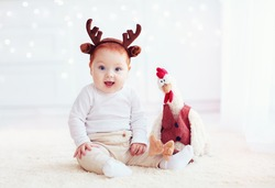 cute baby reindeer and his fellow rooster cock toy on christmas background