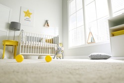 Cute baby room interior with crib and big window, low angle view