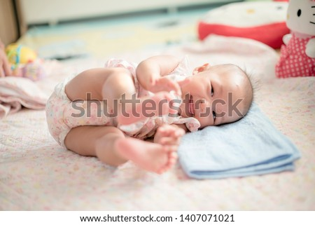 Photo of  Cute Baby 's rolling time with smile. Baby is playing on bed. Baby is laughing