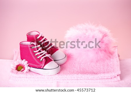 Cute baby shoes, towels, flower over pink background