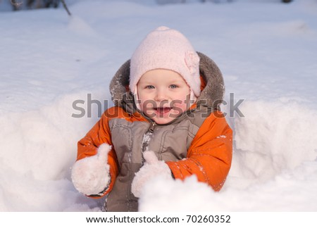 Cute baby sit in snow hideout in forest and dig snow with mittens
