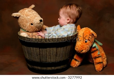 cute baby sitting in barrel with stuffed animal toys