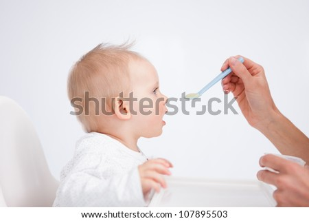 Cute baby sitting on a highchair while being fed against a grey background