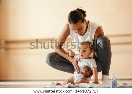 Cute baby sitting on exercise mat while being with his mother in a health club.
