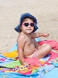 Cute baby sitting on the beach in sun glasses in the form of hearts