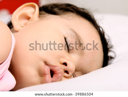 Cute baby sleeping on a white pillow