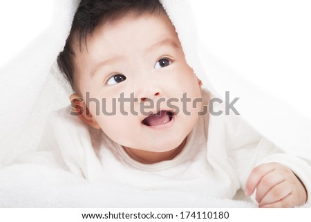 cute baby smiling under a white blanket or towel