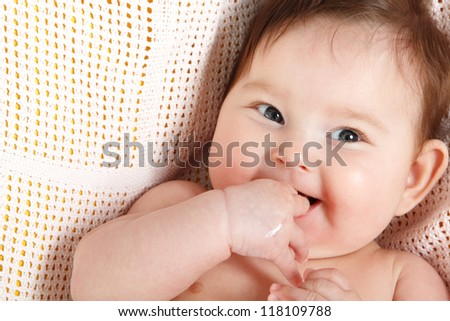 Stock Photo cute baby sucking fingers like a whistles lying on pink plaid, beautiful kid's face closeup 3 month old