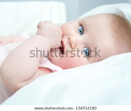 cute baby sucks his thumb lying in bed