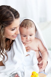 Cute baby taking a bath wihile his mother takes care of him at home