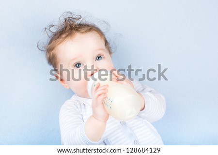 Cute baby with a milk bottle on a blue blanket