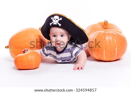 Cute baby with a pirate hat on his head lying on his stomach on a white background including pumpkins on Halloween, picture with depth of field