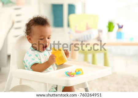Cute baby with bottle of water sitting on chair indoors Stock foto ©