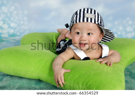 Cute baby with cap lying on a green star-shaped pillow