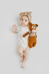 Cute baby with knitted toy. Top view of adorable stylish baby with knitted toy bear looking at camera while lying on gray background