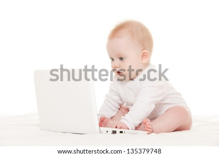 Cute baby with laptop on the white bed