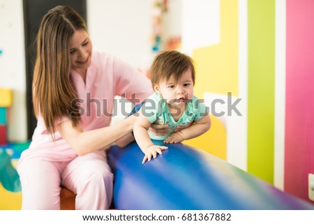 Cute baby working on her balance while crawling on a beam in an early stimulation and development school