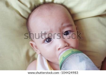 Cute bald baby boy drinking milk from bottle.