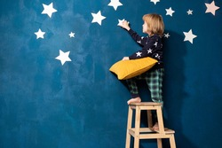 Cute barefoot little boy in pyjamas stays on wood stairs ladder with yellow soft pillow on background of blue bedroom wall decorated by white stars. Caucasian kid in sleepwear dreaming, touching star.