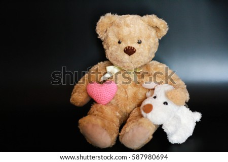 cute bear and dog with pink heart on black background. isolated. #587980694