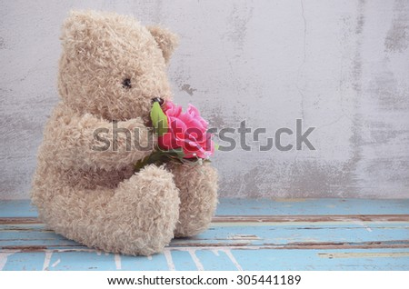 cute bear doll holding rose bouquet