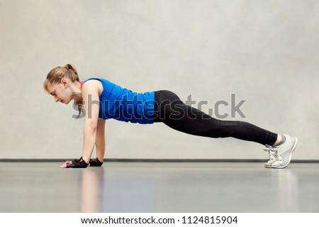 Stock Photo Cute beautiful blonde with blue eyes in a blue sports Jersey doing exercises on the floor. Girl athlete doing push-UPS in the gym. side view