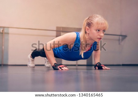 Stock Photo Cute beautiful blonde with blue eyes in a blue sports Jersey doing exercises on the floor. Girl athlete doing push-UPS in the gym.