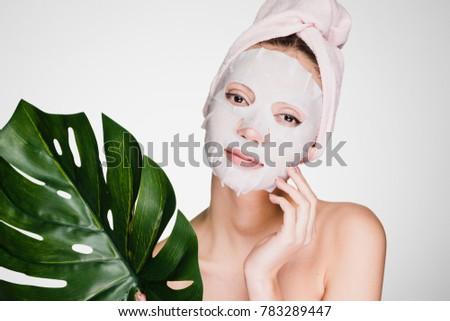 cute beautiful girl with a towel on her head, on her face a tissue mask, holds a green leaf, a spa procedure #783289447
