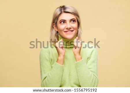 Cute beautiful girl with bright make up and nose ring having excited facial expression, keeping fists clenched, participating in contest, hoping to win, her eyes expressing anticipation and impatience