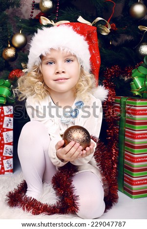 cute beautiful little girls in winter clothes posing beside a  christmas tree and presents