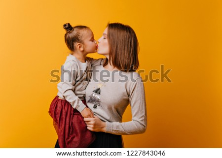 Cute, beautiful, mom and daughter in identical New Year sweaters kiss each other on an isolated orange background. Mom keeps her little daughter in her arms.