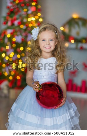 Stock Photo Cute beautiful young girl in airy fairy white dress with stylish blond curly hair close to Christmas New Year tree with big red xmas ball toy and Teddy bear smiling and celebrating holidays.