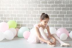 Cute beautiful young little girl ballerina dancer in pink leotard and tutu ballet dress costume sitting on the floor in studio wearing and tie her ballet slipper shoe for ballet dance practice.