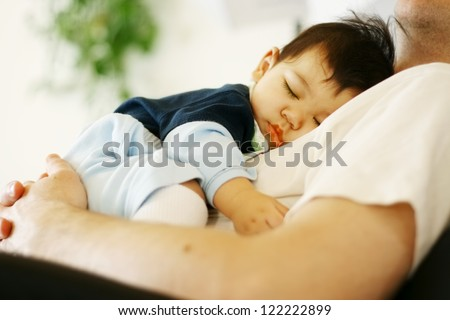 Cute biracial baby boy asleep on father's chest