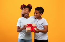 Cute black boy brother making Birthday surprise for his sister, closing her eyes and giving her gift box, yellow studio background, copy space. African american siblings having Birthday celebration