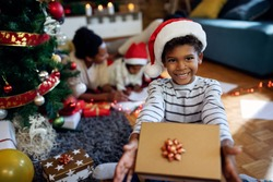 Cute black boy wearing Santa hat and holding gift box on Christmas day at home. His family is in the background.