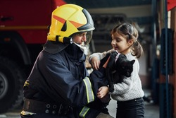 Cute black cat. Happy little girl is with male firefighter in protective uniform.