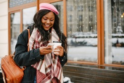 Cute black woman have fun in a city. Beautiful black girl in a pink beret. Stylish lady drinking a coffee. Famale use the phone