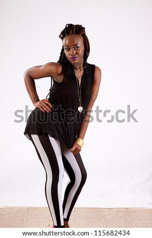 Cute black woman in black and white striped pants,  with her hand on her hip, looking into the camera with a serious expression